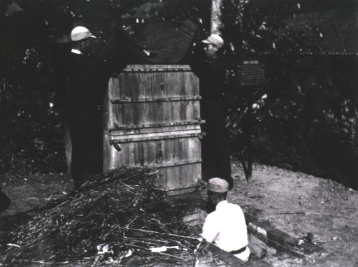 <p>Exterior view: two men facing each other are standing by a wooden apparatus holding a mat while a third man facing the apparatus is partially below ground.</p>