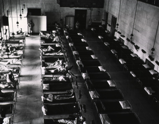 <p>Overhead view of a large room serving as a patients' ward.  Four rows of beds, some occupied by wounded servicemen, fill the room.</p>