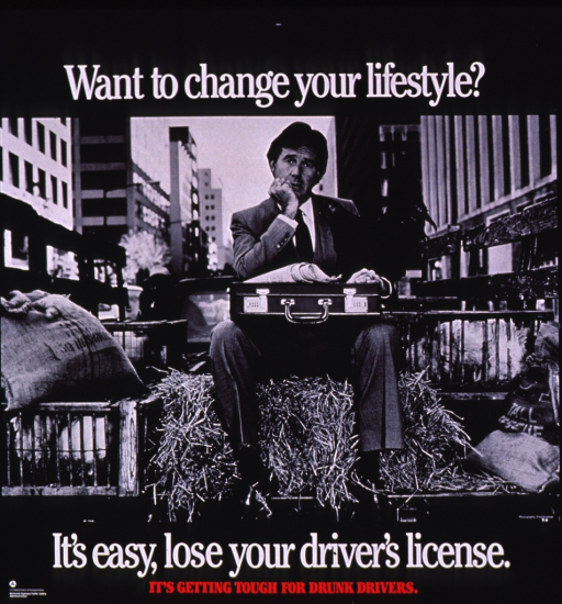 <p>Predominantly b&amp;w poster with white and red lettering.  Title at top of poster.  Visual image is a b&amp;w photo reproduction featuring a man wearing a business suit riding in the back of a pickup truck.  He shares this space with a bale of hay, two bags of feed, and three chicken coops.  Caption and publisher information at bottom of poster.</p>