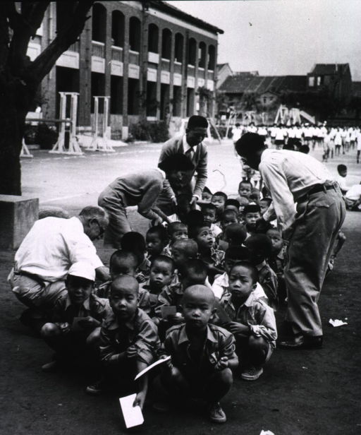 <p>A group of children are squatting on the ground outside a building; they each hold a card which is being examined by four adults.</p>