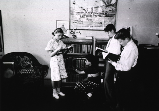 <p>Showing four students reading and selecting books in the library.</p>