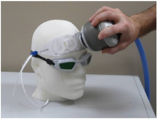 The picture shows the handheld portion of the NeuroThera device, which is pressed against the forehead of the subject. A paper band is used to locate the sites of irradiation across the forehead. Prior to irradiation on each site, the corresponding area of skin is exposed by peeling off the overlying circle of paper from the band.