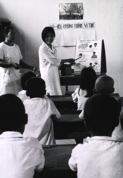 <p>Interior view of a classroom: a young woman, pointing to an illustration on a flip chart, is lecturing to schoolchildren.</p>