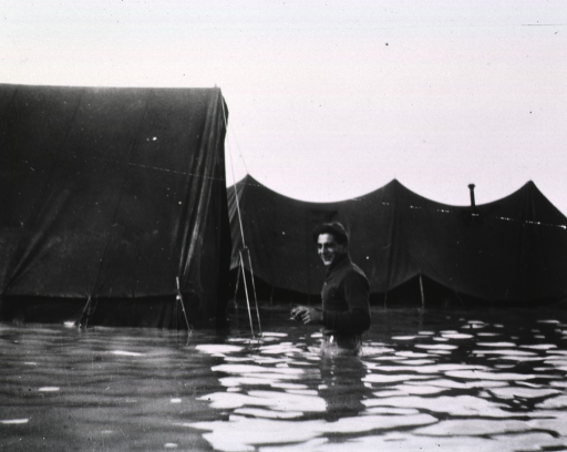 <p>A serviceman walks past tents in water that rises to his waist.</p>