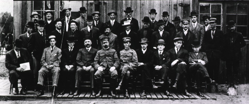 <p>Group portrait, facing front, of Rupert Blue (front row, fifth from left), another U.S. Public Health and Marine Hospital Service officer (front row, sixth from left)  and unidentified public health service workers (?), in front of an unidentified building.</p>
