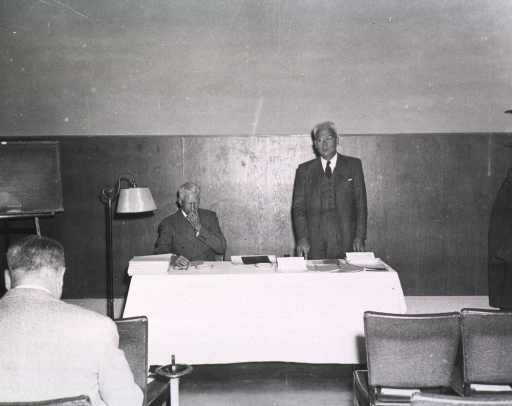 <p>Interior view:  Dr. Chauncey Leake, standing, is presiding at the fifth annual meeting of the Association of the Honorary Consultants to the Army Medical Library.  Col. Harold Jones is seated at the table.</p>