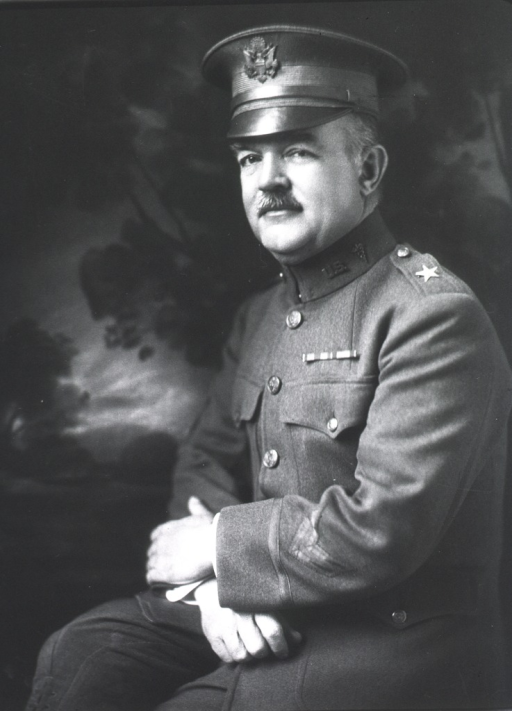 <p>Three quarter length, seated, hands crossed in lap, wearing uniform and cap.</p>