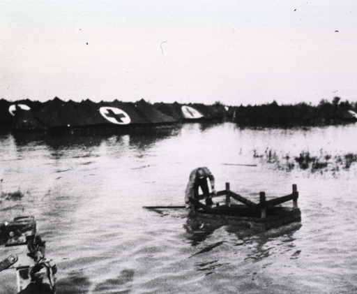 <p>A serviceman attempts to overturn a wooden structure in waters that inundate a field and partially submerge hospital tents.</p>