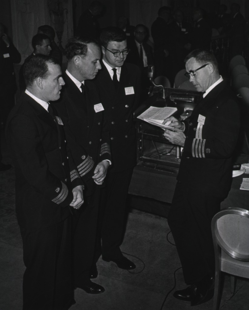 <p>Photograph of, from left to right, Dr. Baruch Blumberg, NIAMD, Dr. Donald Fredrickson, NHI, Dr. Bert N. La Du, NIAMD, and Dr. T.J. Kennedy, OD, NIH.  Dr. Kennedy presided over the session of the meeting at which Drs. Blumberg, Fredrickson, and La Du presented papers.  All four men are dressed in their winter uniforms.  Other men in civilian suits are in the background</p>