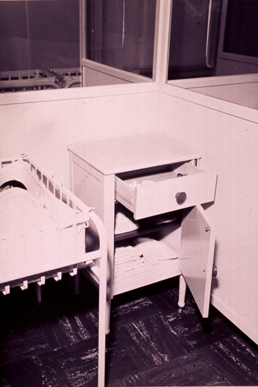 <p>An infant in a hospital nursery which is divided into individual cubicles with a cabinet for equipment.</p>