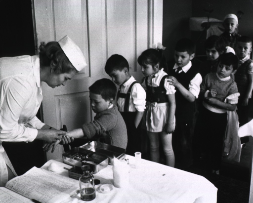 <p>A line of children await their turns as a nurse vaccinates a young boy.</p>