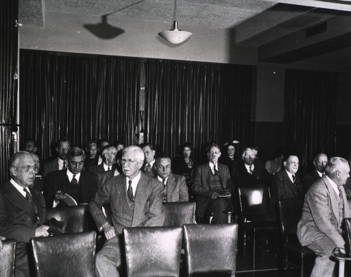 <p>Interior view:  Members and friends seated at the fifth annual meeting (1948) of the Association of the Honorary Consultants to the Army Medical Library.  Henry Viets is filling his pipe, a chair separates him from Harold Jones.</p>