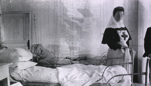 <p>A nurse stands near a bed in the officer's ward aboard a floating hospital.</p>