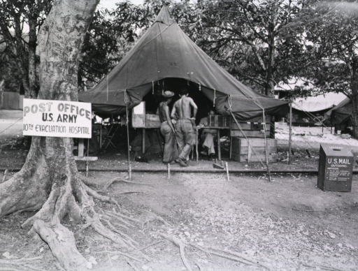 <p>Two shirtless men stand in the opening of a tent. A man in uniform sits behind a table in the tent.  A sign is posted on a tree that stands next to the tent: Post Office, U.S. Army ...</p>