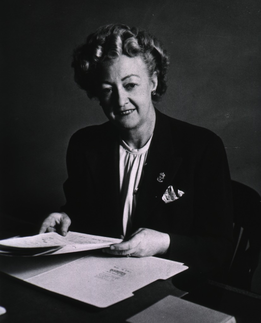 <p>Half length, seated at desk, holding papers, full face.</p>