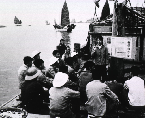 <p>A group of men are sitting on the deck of a boat; standing before them is a young woman; hanging on the mast is a health education poster.</p>