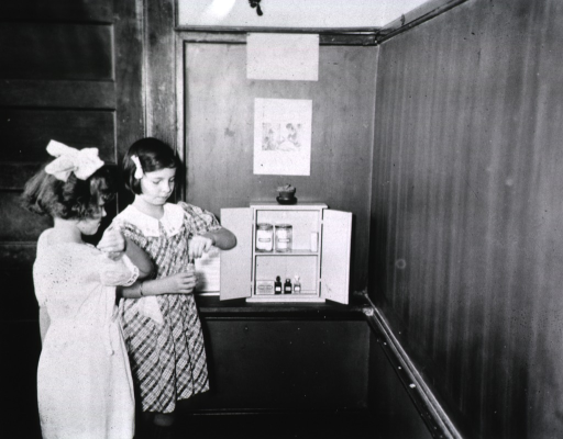 <p>Showing two girls using items from the first aid kit.</p>