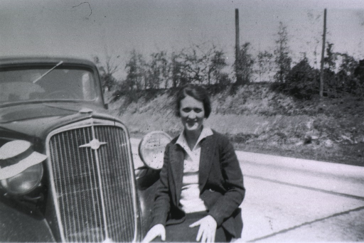 <p>West Florida staff nurse, 1930, sitting on the front fender of a car.</p>
