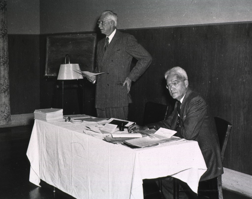<p>Interior view:  Col. Harold Jones is standing at the head table with his hand on his hip addressing the fifth annual meeting (1948) of the Association of the Honorary Consultants to the Army Medical Library.  Dr. Chauncey Leake is seated next to him at the table.</p>