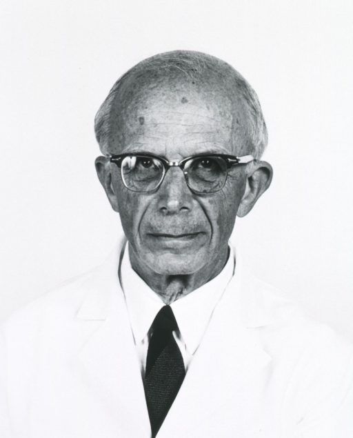 <p>Head and shoulders, full face; wearing white lab coat and glasses.</p>