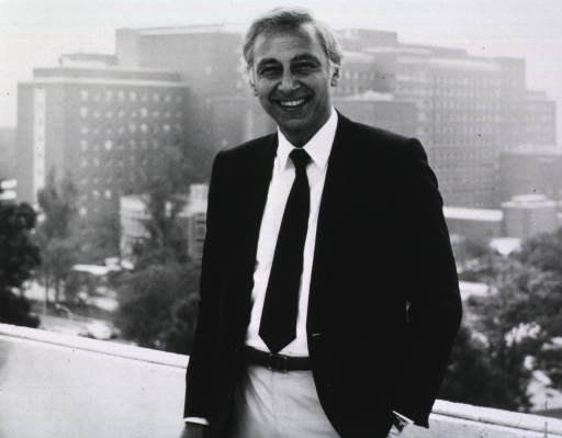 <p>Gallo, shown half-length, left pose, full face, stands on the balcony or roof a building on the NIH campus; the Clinical Center is in the background.</p>