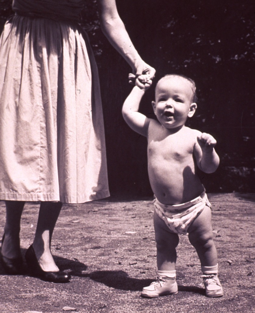 <p>An infant, standing, is holding on to the finger of a woman.</p>