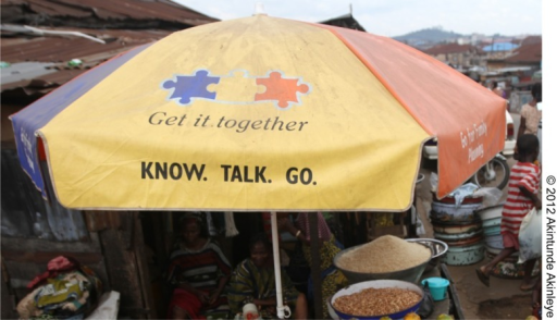 "A roadside market umbrella in Mapo district in Ibadan, Nigeria, branded with the ""Get it Together"" NURHI puzzle logo, encourages people to ""know"" about family planning, ""talk"" with their partner about it, and ""go"" for family planning services."