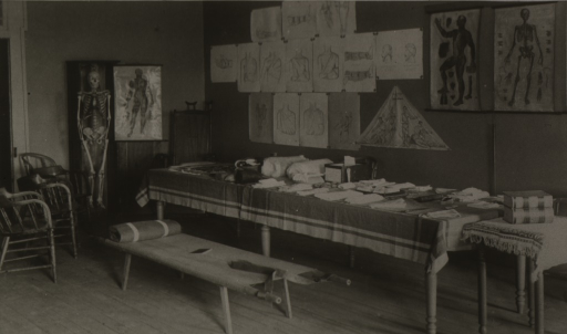 <p>The lecture room at Fort Union, New Mexico, with table covered with bandages, stretcher, and 18 posters showing methods of bandaging.</p>