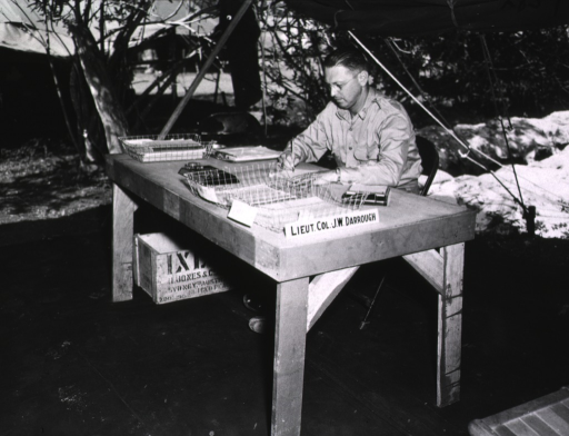 <p>Lieutenant Colonel J.W. Darrough sits behind a desk in a tent and writes on a piece of paper.  A label with Darrough's name sits prominently on the desk.</p>