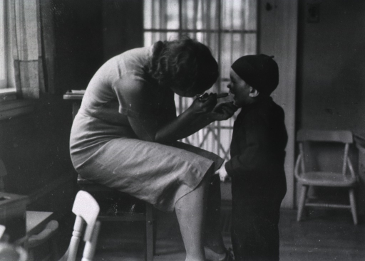 <p>Showing a nurse examining a small boy's throat.</p>