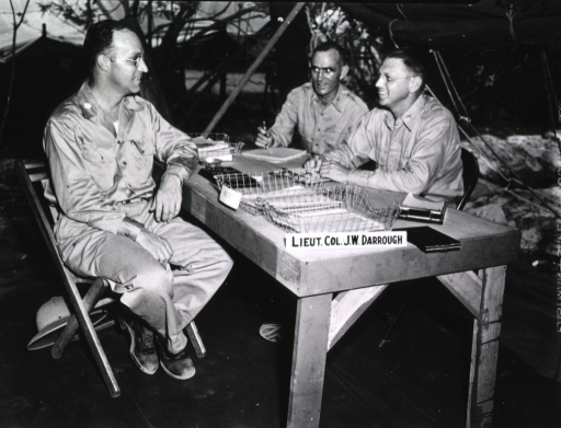 <p>Lieutenant Colonel J. W. Darrough, C.O. and Chief of Services, sits at a table and chats with two unidentified military personnel in uniform.  Darrough's nameplate is displayed prominently on the table.</p>