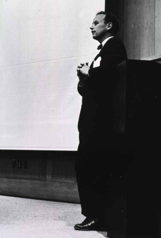 <p>Donald Fredrickson, head of the section on molecular disease at the National Heart Institute (NHI), is leaning against a podium with his hands folded in front of him.  There is an extended movie screen to his right.</p>