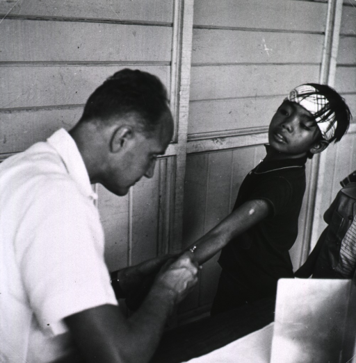 <p>A young boy is being vaccinated by a physician.</p>