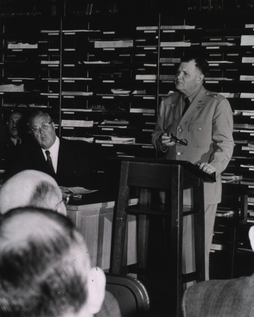 <p>Interior view:  The opening session of the 8th annual meeting.  Brig. Gen. Silas B. Hays, deputy surgeon general, is at a podium in front of the serials stacks in the Library Hall reading room.  Seated left to right are Lt. Col. Frank B. Rogers, director of the AML, and Dr. Wilbert C. Davison, president of the Association of Honorary Consultants to the Army Medical Library.</p>