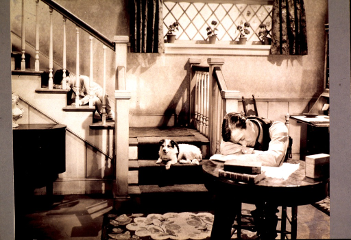 <p>A man sits slumped over a table, his head in his arms, before papers and books.  Behind him on the stairs sits an alert dog.  Higher up the stairs, a little boy in pajamas sleeps.</p>