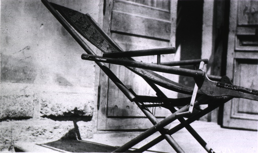 <p>A German Red Cross Hospital invalid chair sits outside the Hospital door.</p>