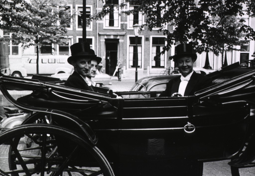 <p>Exterior view: three men, wearing top hats, are riding in a carriage; the man on the right is on his way to defend his doctoral thesis, the other men act as seconds, offering moral support.</p>
