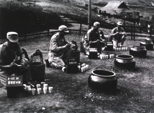 <p>Exterior view: wooden buckets are next to knealing men pouring from bottles into spoons; white containers are next to open boxes with NE XVI-4 written on top; large cylinders are imbedded in the ground.</p>