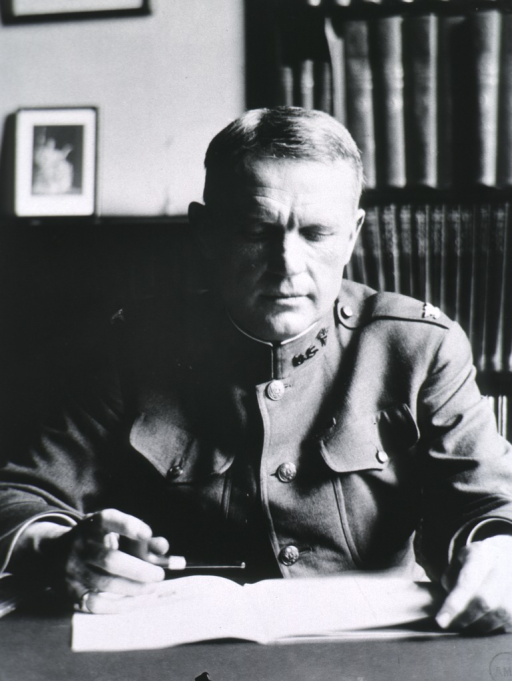 <p>Seated at desk, reading, head down, in uniform.</p>