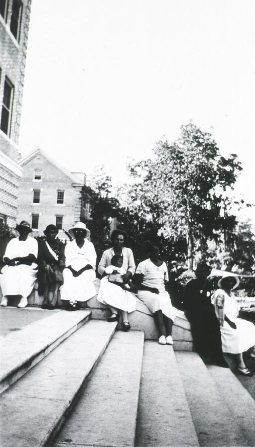<p>Showing group of African American midwives sitting on the steps' stone railing in 1933.</p>
