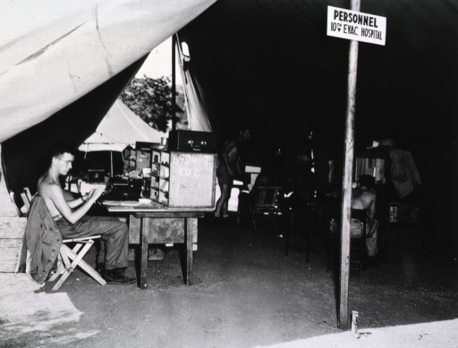 <p>Several shirtless men are shown at work at tables in a tent.  One of the men sits and types.  A sign indicating the name of the office is posted on one of the tent poles.</p>