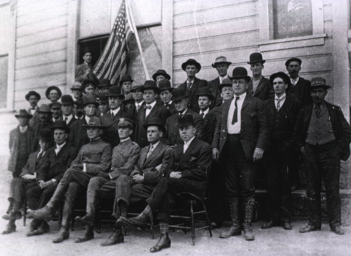 <p>Group portrait of two men in United States Public Health and Marine Hospital Service uniforms (seated, front row) and other men in civilian clothes posing in front of a building; a man in a window behind them holds the end of a U.S. flag and a sign in the window identifies the building as the United States Public Health and Marine Hospital Service Headquarters Provisional Plague District.</p>