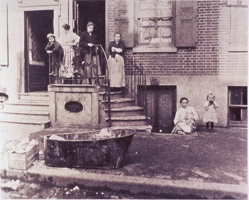 <p>Exterior view of a building; a woman holding a baby is sitting on the steps leading to the basement of the building.</p>