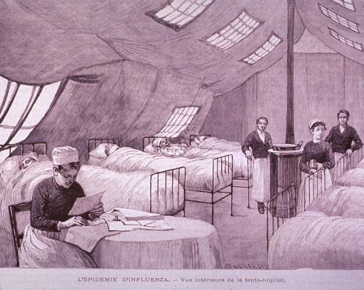 <p>Interior view of supplemental tent hospital showing a nurse sitting at a table, several beds with patients, and nurses standing near a stove.</p>