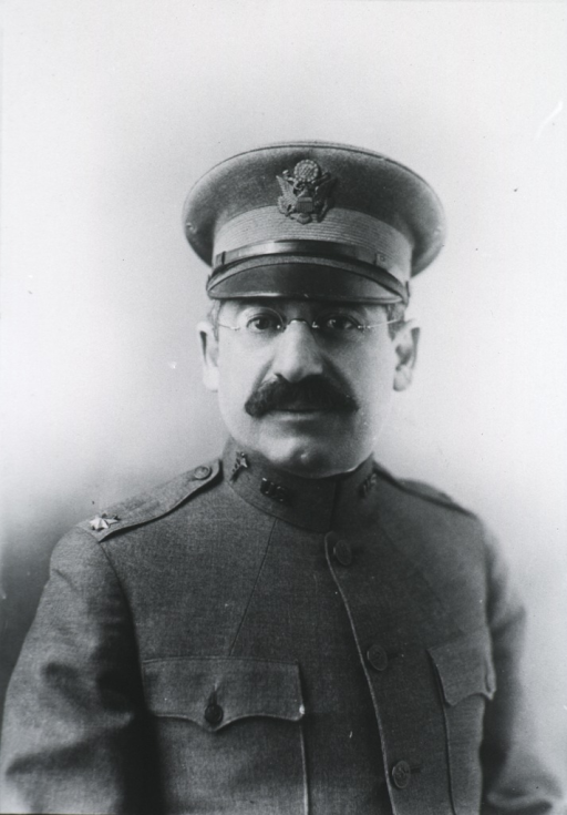 <p>Head and shoulders, right pose, full face; wearing glasses, uniform and cap.</p>
