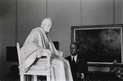 <p>Donald S. Fredrickson is standing next to a statue of Voltaire at the Hermitage Museum in Leningrad.  Seated in a chair, a smiling Voltaire is leaning forward.  Three works of art are hanging on the wall behind Dr. Fredrickson.</p>
