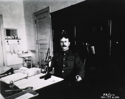 <p>Half-length, seated at desk, full face; wearing uniform and glasses; microscope in front of him on the desk; book cases behind him and a sink in the corner in the background.</p>
