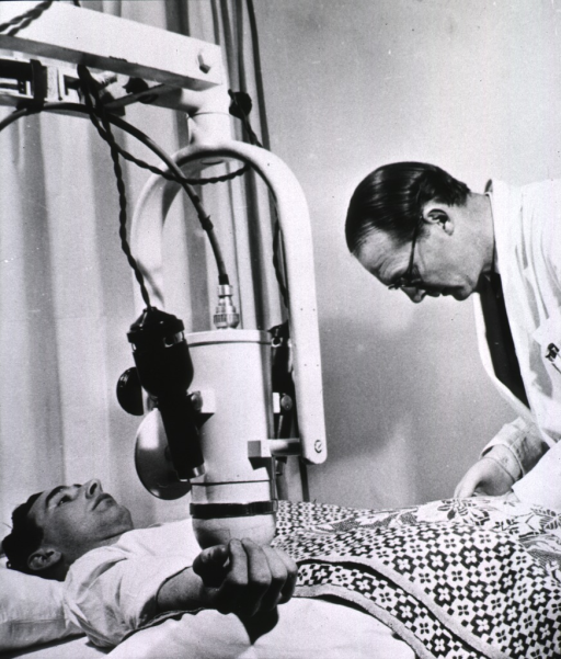 <p>The circulation time from wrist to wrist is being measured by means of radioiodine: a patient is lying on a bed with a monitoring device suspended over his right wrist.</p>