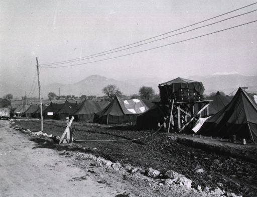 <p>A row of tents is pitched next to a dirt road.  A water tower stands between two of the tents.  Mountains rise in the distance.</p>