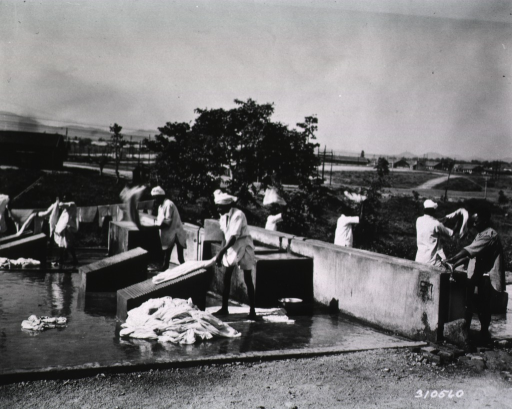 <p>A group of men do laundry outdoors on a cement platform.</p>